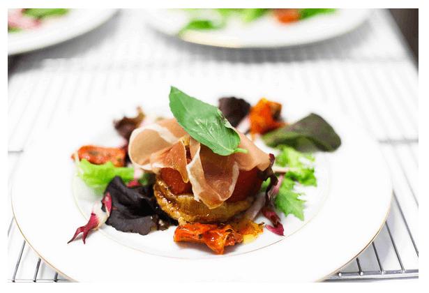 Tatin de tomates fraîches et confites au basilic, mesclun aux herbes et chiffonnade de Bayonne.