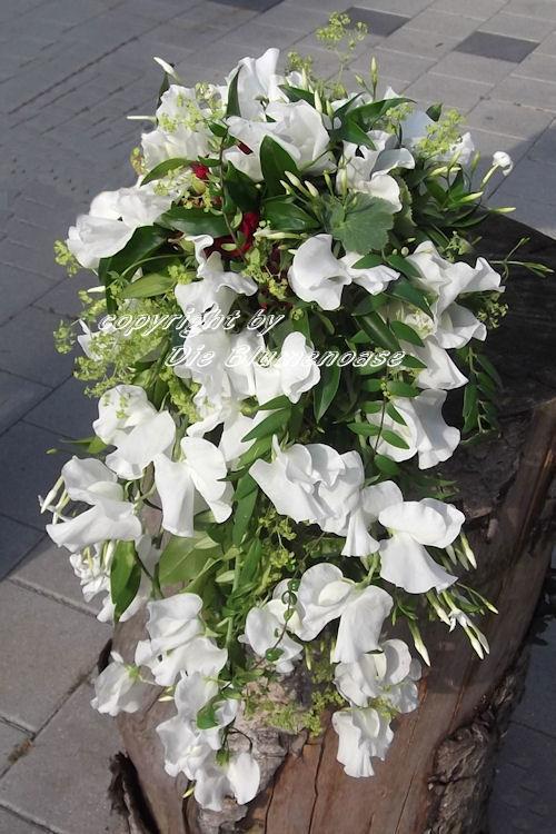 Beispiel: ganz leicht in Weiss, mit einem Akzent Rot, abfließendee Brautstrauß, Foto: Die Blumenoase.