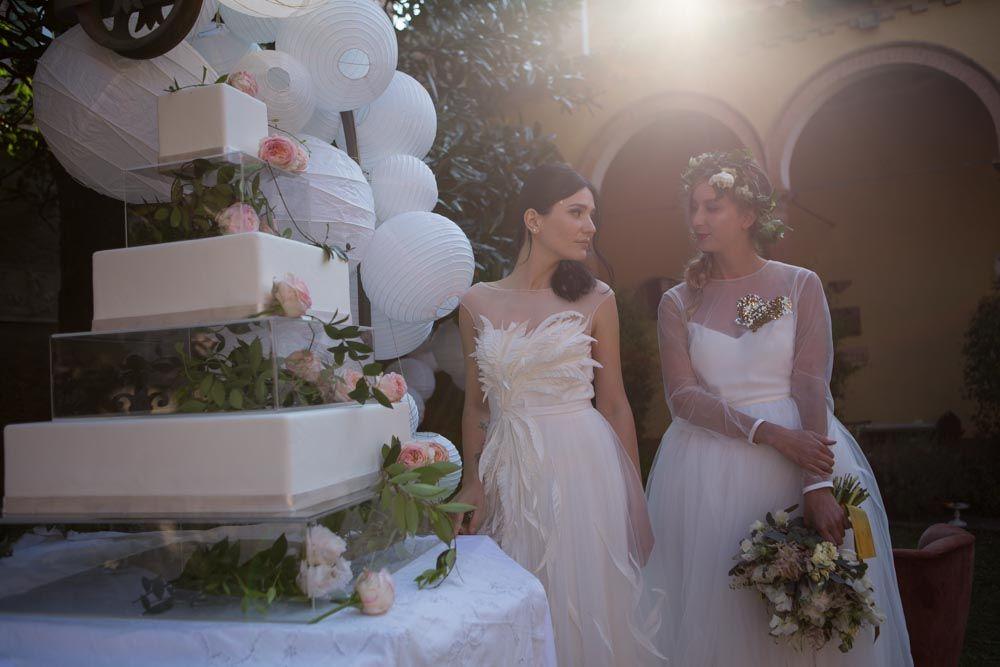 Le spose si avvicinano alla torta nel giardino d'ingresso