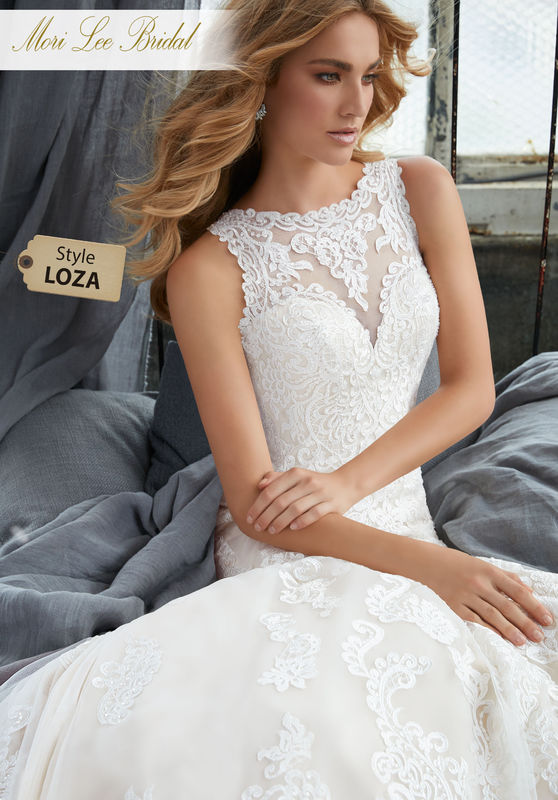 Style LOZA  Krista Wedding Dress  Romantic Fit and Flare Gown Featuring Frosted, Embroidered Medallions and Appliqués on Net. A Beautiful Illusion Back Trimmed in Covered Buttons Complests the Look. Available in Three Lengths: 55″, 58″, 61″. Colors Available: White, Ivory, Ivory/Crème