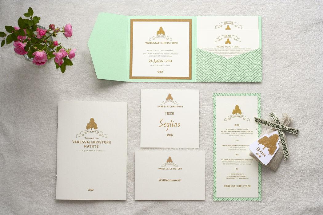 Papeterie für eine schweizer Berghochzeit Pocketfoldkarte in gemustertem Mint, Bronze und Creme, mit zwei Einlegern  Kirchenheft, Tischkarte, Willkommenskarte, Menükarte als Flachkarte, Gastgeschenkanhänger in Baumform,