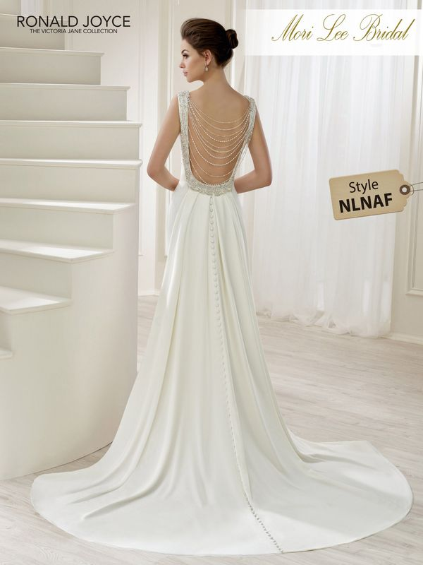 Style NLNAF LAILA  AN ELEGANT CREPE DRESS WITH A BEADED NECKLINE AND BACK BUTTON DETAIL. DRESS COMES WITH DETACHABLE BACK BEADS AND A MATCHING TRAIN. PICTURED IN IVORY.  COLOURS WHITE, IVORY