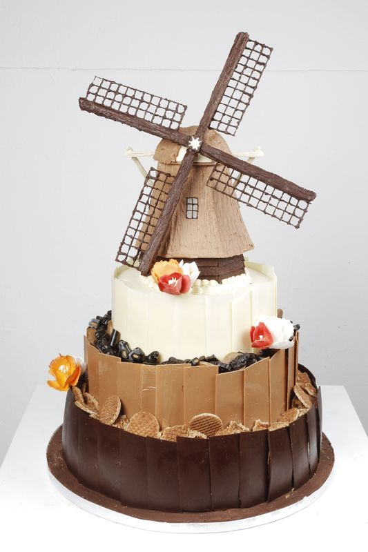 Bruidstaart met een hollands thema. De taart is gedecoreerd met chocolade schotsen en boven op de taart een molen geheel gemaakt van chocolade.